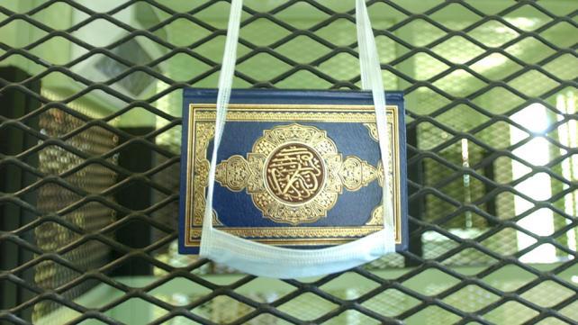 A Koran hung in a surgical mask, in Guantanama