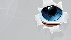 eye peering through a paper hole